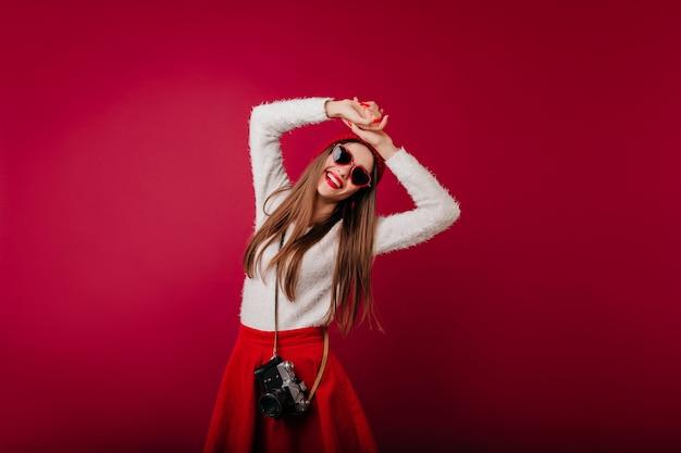 Menina elegante com chapéu e óculos de sol relaxando durante a sessão de fotos do estúdio