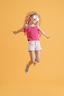 Menina elegante com dreadlocks rosa pulando sobre um fundo amarelo