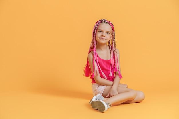 Menina elegante com dreadlocks rosa sentado