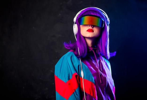 Menina elegante com óculos cyber punk e agasalho com fones de ouvido na parede escura