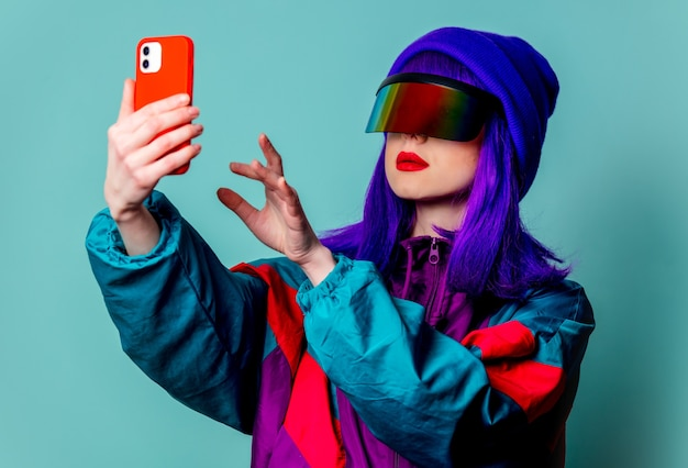 Menina elegante com óculos cyber punk e agasalho de treino usando o celular na parede azul