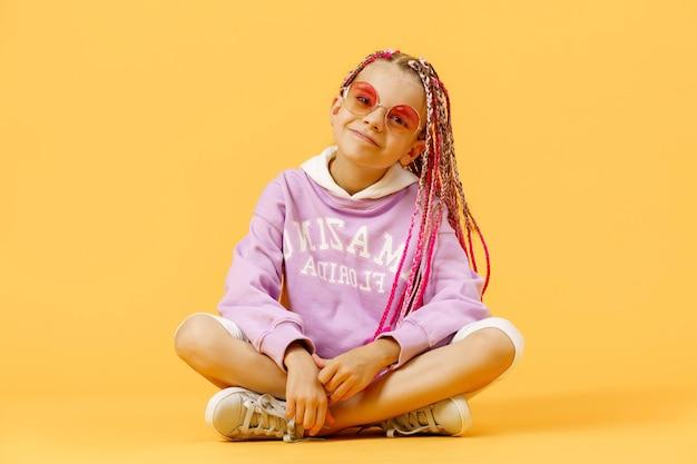 Menina elegante com óculos redondos e dreadlocks rosa sentada