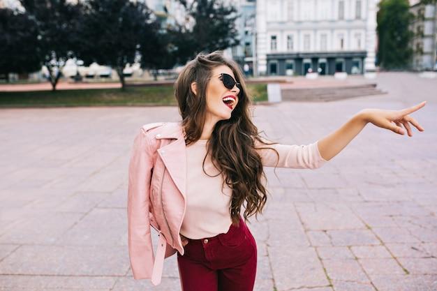 Menina elegante com penteado longo em calças vínicas se divertindo na cidade. ela tem uma jaqueta rosa no ombro, aparecendo de lado.