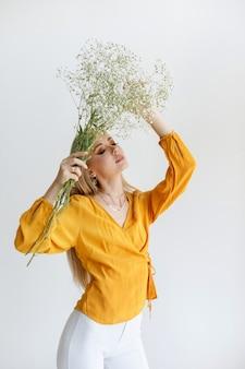 Menina elegante com um buquê de flores secas, posando sobre um fundo claro