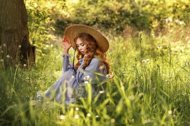 Menina elegante com um chapéu no jardim no verão em uma caminhada