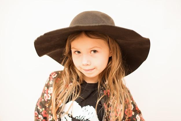 Menina elegante com um grande chapéu preto na parede branca