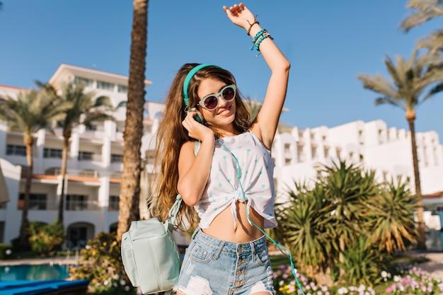 Menina elegante com um lindo penteado usando óculos escuros e shorts jeans, posando alegremente em frente ao prédio e palmeiras nas férias de verão