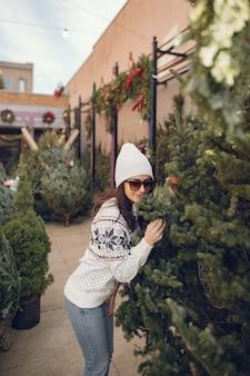 Menina elegante compra uma árvore de natal.
