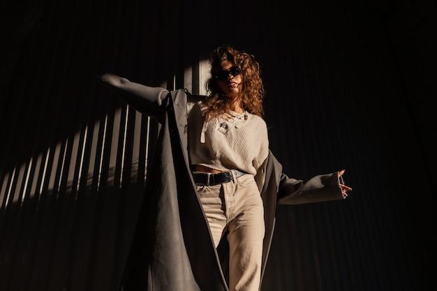 Menina elegante de cabelos cacheados com óculos escuros em um casaco longo da moda com um suéter e calças posa na rua perto de uma parede de metal à luz do sol e na sombra