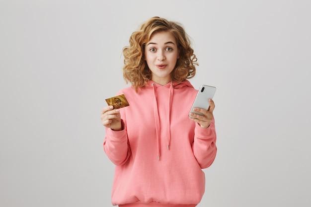 Menina elegante de cabelos crespos fazendo compras online, usando cartão de crédito e smartphone