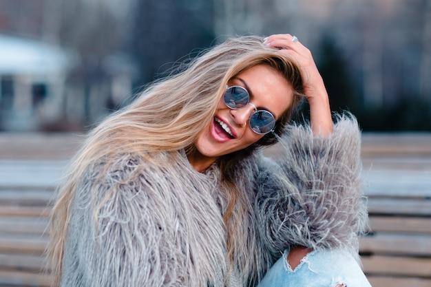 Menina elegante de casaco e óculos de sol na rua