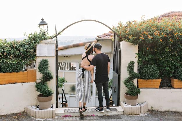 Menina elegante de chapéu beija o namorado em frente a portões pretos com plantas exóticas pela manhã