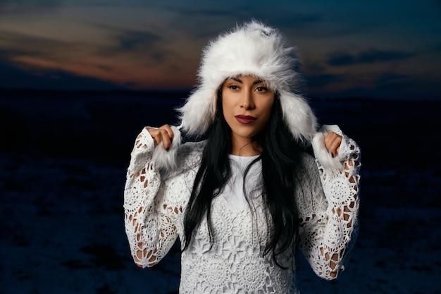 Menina elegante de chapéu branco em campo com neve na noite.