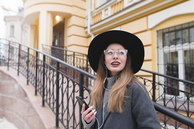 Menina elegante de chapéu e óculos no contexto da arquitetura antiga. garota feliz com aparelho sorri sinceramente