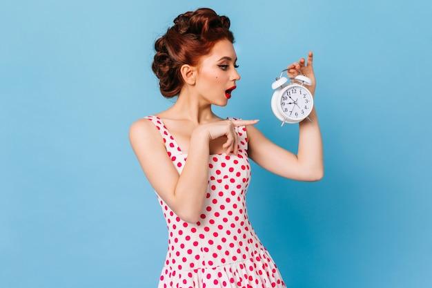 Menina elegante de gengibre apontando com o dedo para o relógio. foto de estúdio de senhora caucasiana em vestido de bolinhas de pé no espaço azul.
