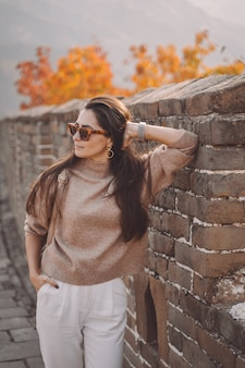 Menina elegante de óculos visitar a grande muralha da china