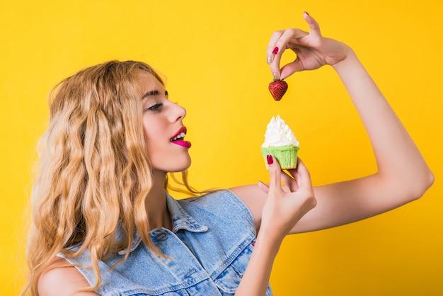 Menina elegante, desfrutando de bolinho com morango.