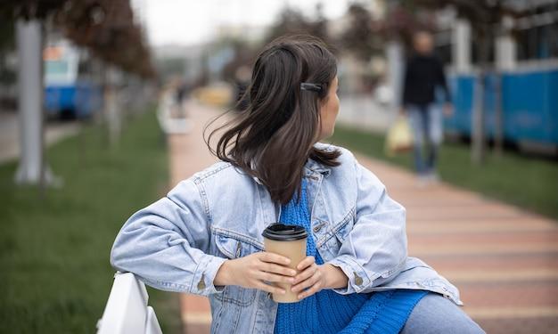 Menina elegante e alegre em estilo casual aprecia um café para viagem durante uma caminhada
