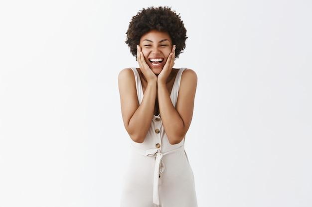 Menina elegante e animada posando contra a parede branca