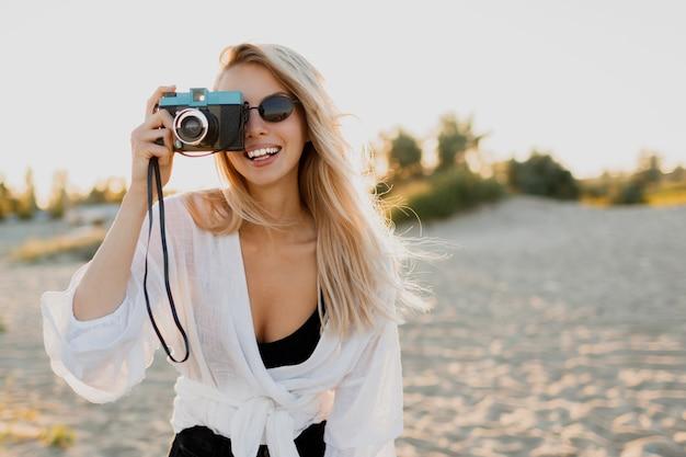 Menina elegante e bem torneada com câmera retro, posando na praia ensolarada. férias de verão. clima tropical. liberdade e conceito de viagens.