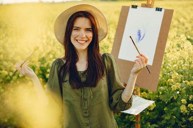 Menina elegante e bonita pintura em um campo