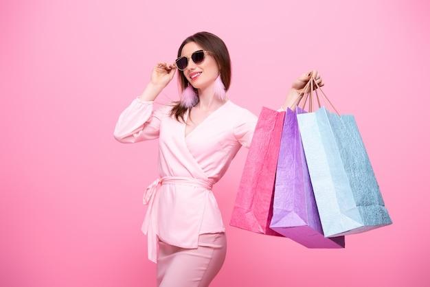 Menina elegante e elegante em óculos de sol com sacolas de compras multicoloridas