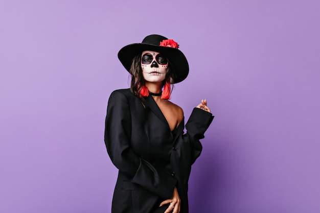 Menina elegante e encaracolada com brincos vermelhos e rosa no chapéu preto de aba larga posando pateticamente com roupa para o halloween.