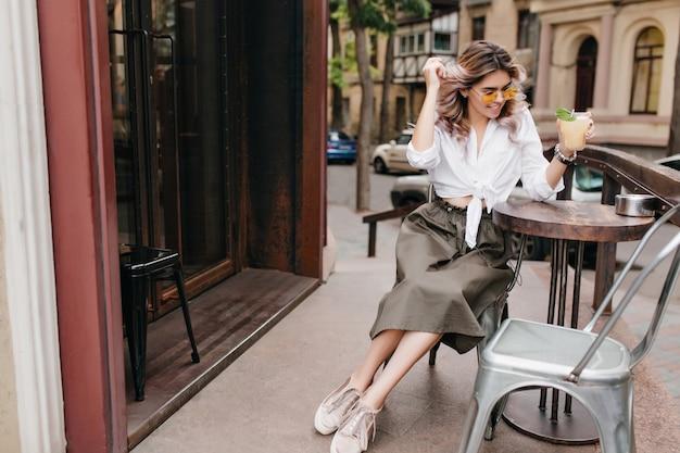Menina elegante e feliz com camisa branca e saia longa bebe chá gelado em um café ao ar livre