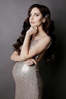 Menina elegante e grávida modelo morena com maquiagem suave, no vestido com lantejoulas douradas, olha para a câmera e posando para o fundo cinza escuro