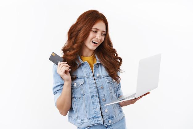 Menina elegante e moderna escolhe uma nova loja de roupas na internet, faz compras online, segura o laptop e acena com um cartão de crédito preto com sorriso satisfeito e encantado, digita o número da conta bancária, olha a tela do notebook