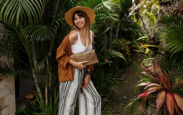 Menina elegante elegante em top branco e chapéu de palha, posando em folhas de palmeira em bali.