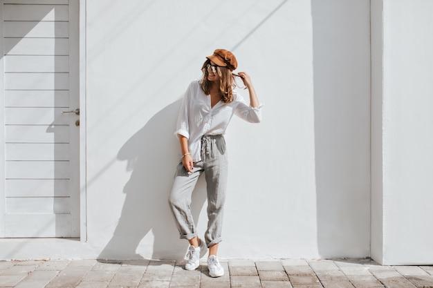 Menina elegante em calça cinza e blusa de algodão branca se passando perto de uma parede branca. mulher de boné e óculos.