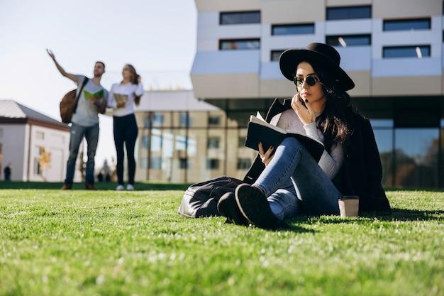 Menina elegante em chapéu preto e casaco fica com livro e café no gramado antes da biblioteca