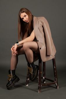 Menina elegante em couro posando na cadeira