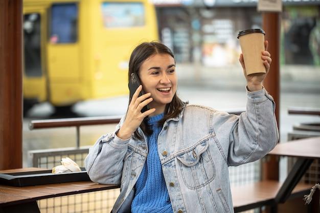Menina elegante em estilo casual fala ao telefone com café na mão e está esperando por alguém.