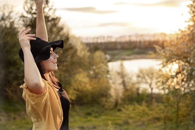 Menina elegante em estilo casual, sorri e olha para o pôr do sol.
