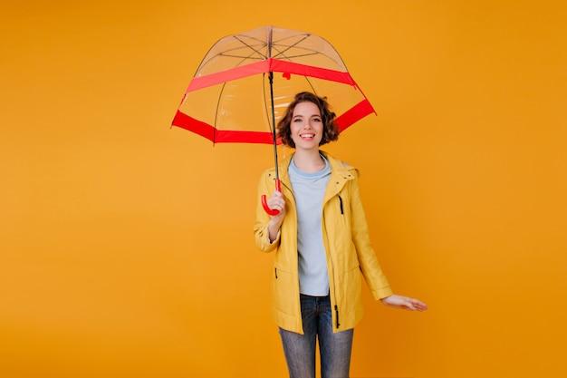 Menina elegante em jeans e capa de chuva em pé sob o guarda-chuva bonito. retrato interior de uma jovem romântica com penteado encaracolado, segurando o guarda-sol na parede laranja.