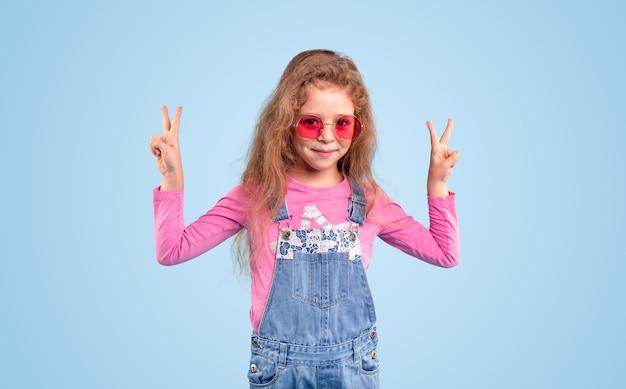 Menina elegante em macacão jeans e óculos de sol rosa da moda, mostrando o gesto de dois dedos e olhando para a câmera contra um fundo azul