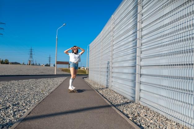 Menina elegante em meias brancas andar de longboard na rua e ouvir música.