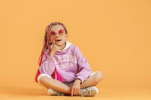 Menina elegante em óculos arredondados com dreadlocks rosa posando em um fundo amarelo
