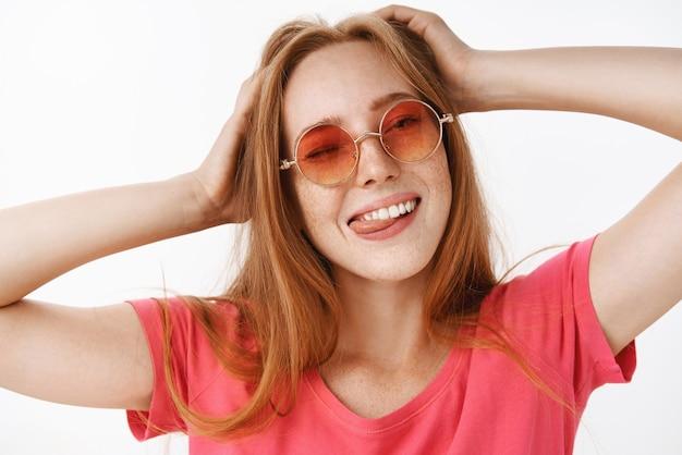 Menina elegante em óculos de sol da moda e camiseta rosa de mãos dadas na cabeça, piscando, mostrando a língua alegremente e sorrindo de alegria e emoções relaxadas, se divertindo, relaxando sobre uma parede cinza