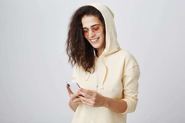 Menina elegante em óculos de sol enviando mensagens de texto no celular e sorrindo