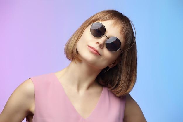 Menina elegante em óculos de sol. sessão de fotos no estúdio em um fundo rosa