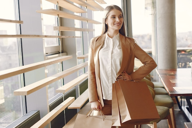 Menina elegante em pé em um café com sacolas de compras