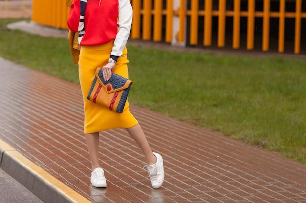 Menina elegante em pé na rua em roupas amarelas brilhantes