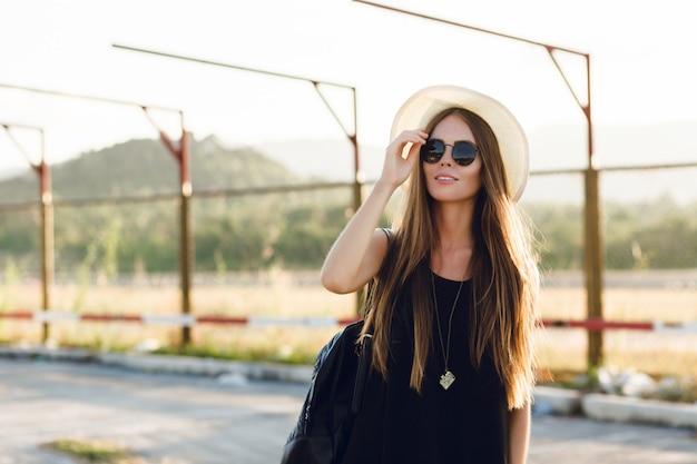 Menina elegante em pé perto da estrada usando vestido preto curto, chapéu de palha, óculos pretos e mochila preta. ela sorri sob os raios quentes do sol poente. ela toca seus óculos de sol com a mão