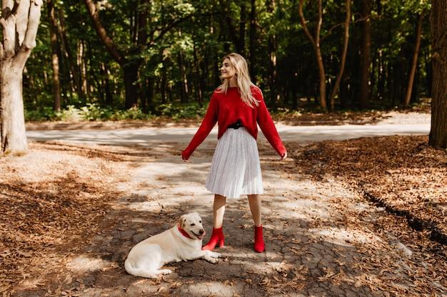 Menina elegante em sapatos vermelhos se divertindo com seu cachorro. loira alegre sorrindo alegremente ao ar livre.