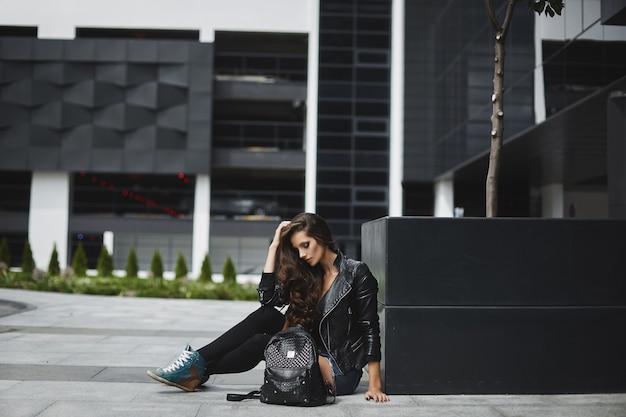 Menina elegante em shorts jeans e uma jaqueta de couro posando em uma rua da cidade em um dia de verão, foto de um ...