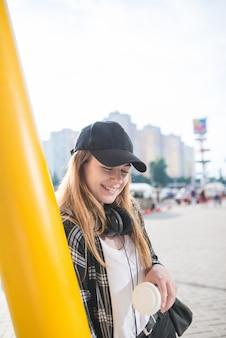Menina elegante em streetwear e fones de ouvido no pescoço, sorri e olha para o fundo da cidade.