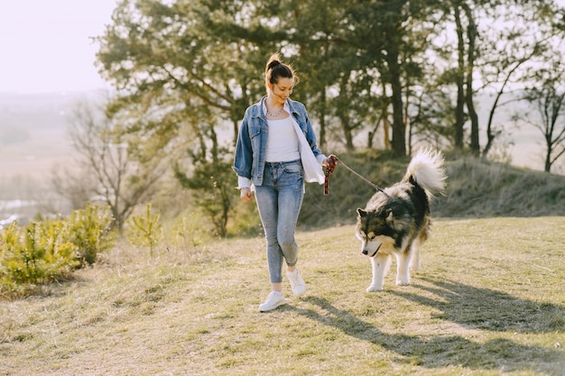 Menina elegante em um campo ensolarado com um cachorro